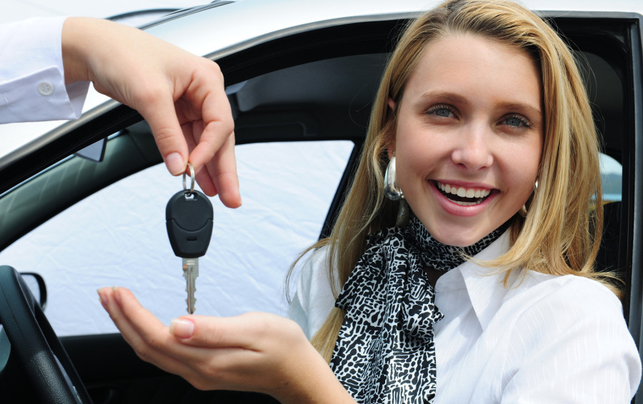 happy woman receiving car key - find a used car