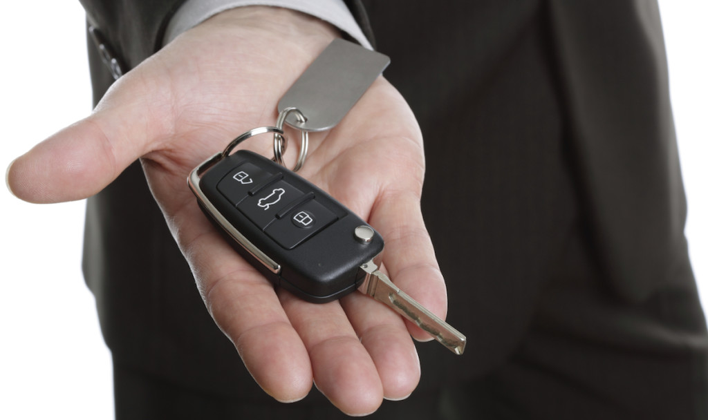 Car salesman or rental man giving over a car key