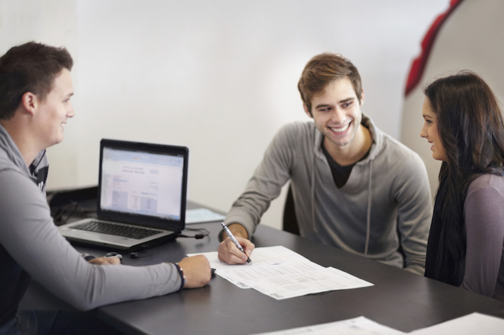 Young couple in a car saleman's office signing paperwork for a new car