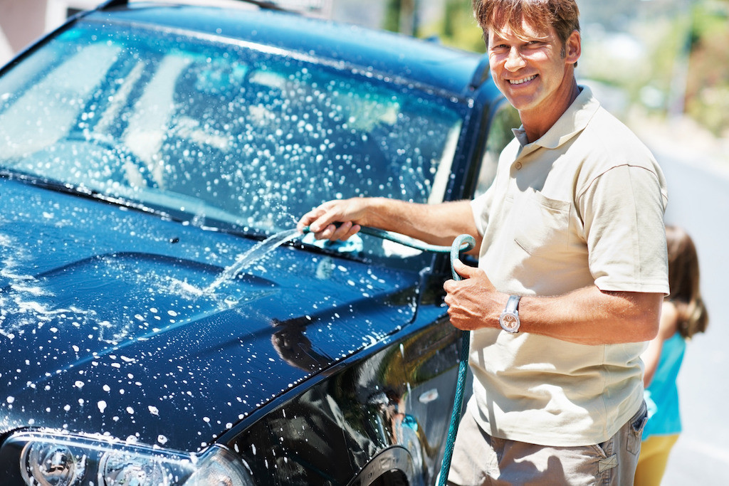 Portrait of man washing his car and smiling with daughter in background