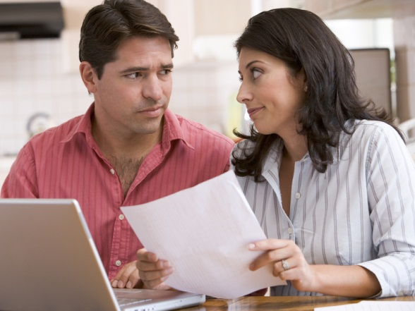 Couple in kitchen with paperwork using laptop looking unhappy