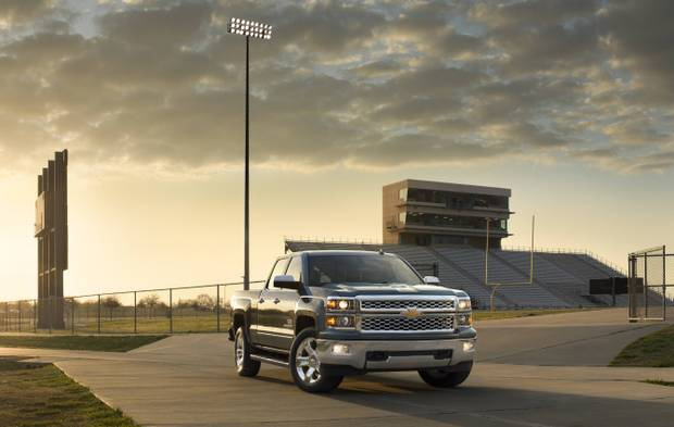 A blue Chevy Silverado in front of a football field at dusk