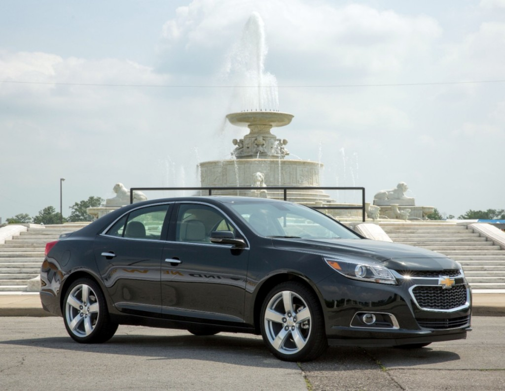 A black Chevy Malibu in front of a fountain