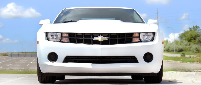 The front of a white Chevy Camaro from the front against a cloudy blue sky