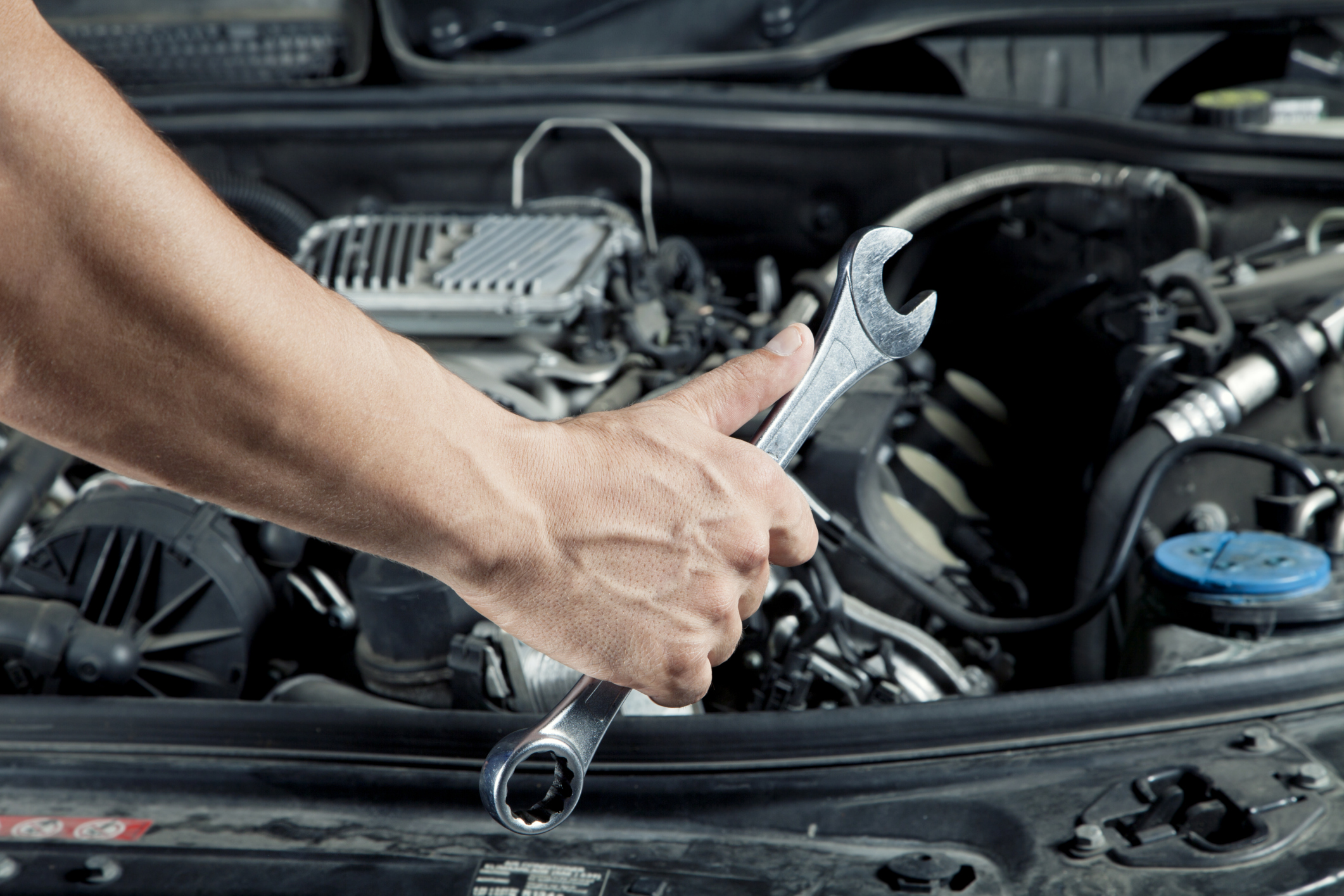 A closeup is shown of a hand holding a wrench in front of a car's engine bay.