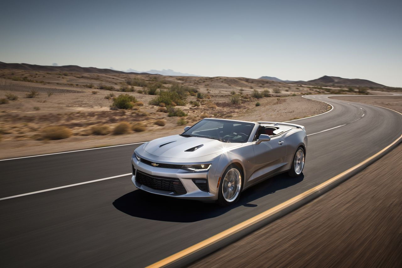 A silver 2016 Chevy Camaro Convertible is driving on a windy desert highway.