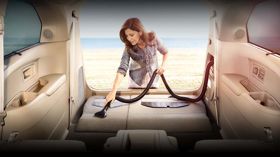 Woman using the built in vaccum in the Honda Odyssey