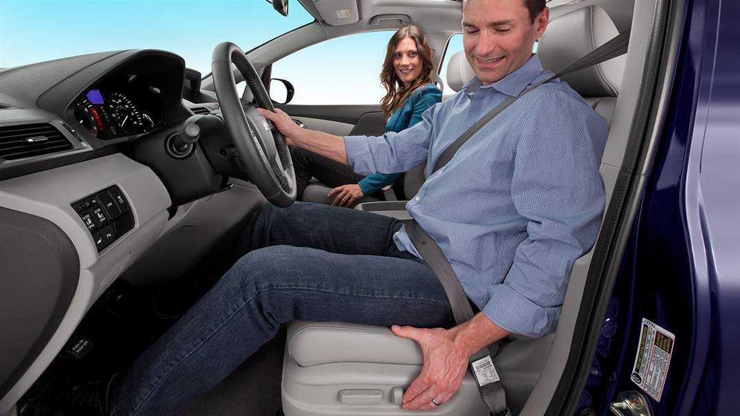 Guy adjusting his drivers seat in a Honda Odyssey