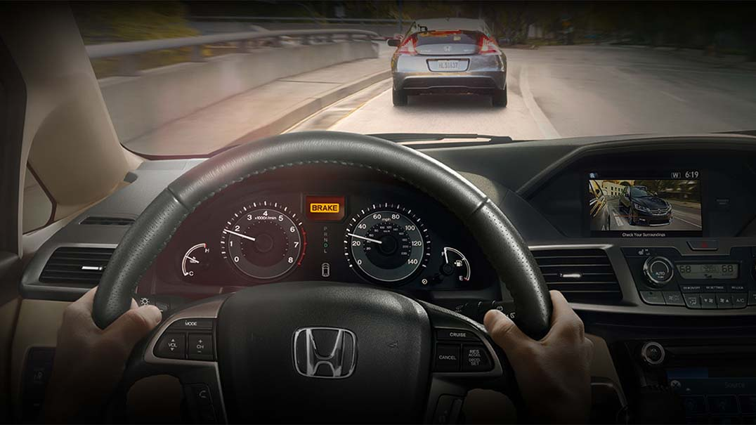 Driver in a Honda Odyssey driving with the forward collision brake system activated
